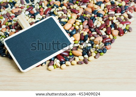 Group of colorful various beans or lentils, nut and whole grains seeds or cereal background. mung bean, peanut or groundnut, blackbean, red kidney bean, soybean, pinto beans. Empty black wood sign. - stock photo
