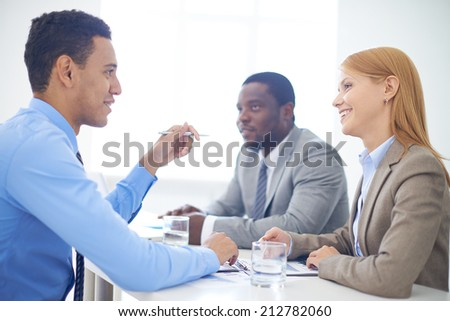 Group of confident business partners interacting at meeting in office - stock photo