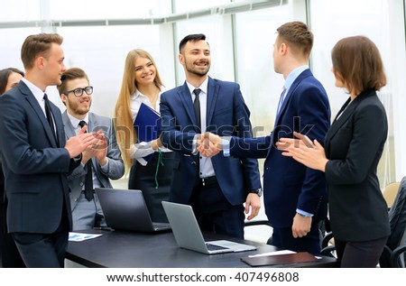 Group of confident business people in formal wear sitting at the table together and smiling while two men handshaking - stock photo
