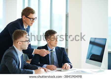 Group of confident businessmen looking at computer monitor