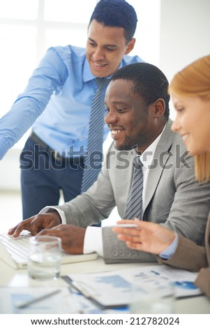 Group of confident employees discussing computer project - stock photo