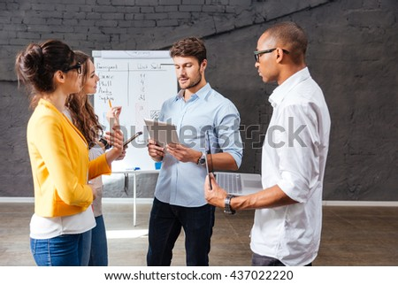 Group of confident young people standing and discussing new project in conference room - stock photo