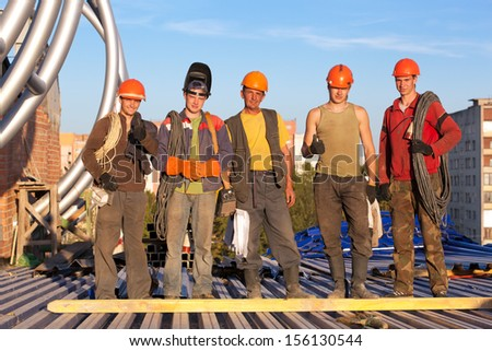 Group of construction workers at building site - stock photo