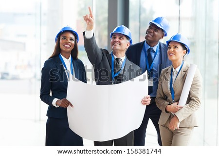 group of construction workers holding blue print and discussing project - stock photo