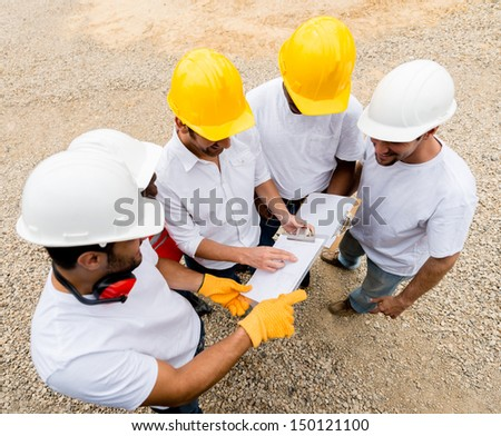 Group of construction workers talking at a building site  - stock photo