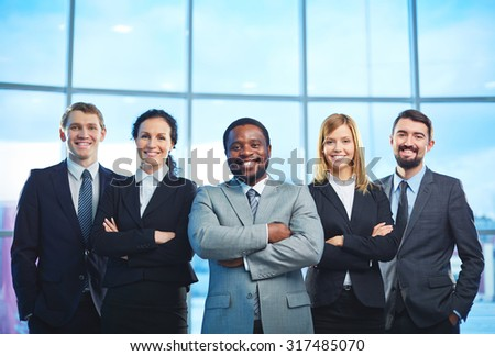 Group of contemporary business partners in formalwear looking at camera with smiles - stock photo