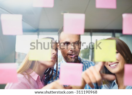 Group of corporate people brainstorming  on new project with many sticky notes on window - stock photo