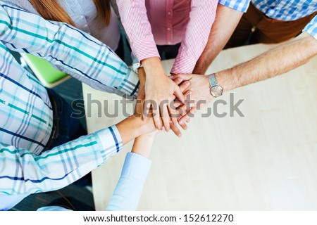 Group of corporate people working on new project joining hands over table - stock photo