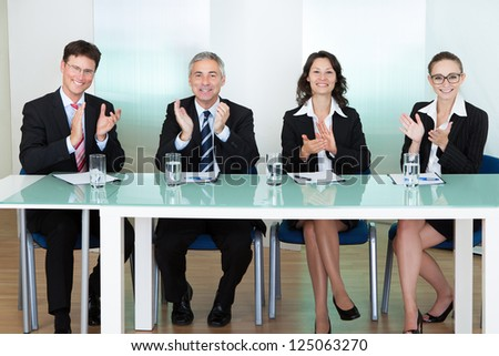 Group of corporate recruitment officers interviewing for a professional vacancy applauding - stock photo