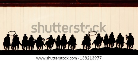 Group of cowboys on horses in vintage style