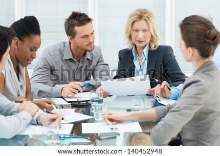 Group Of Coworkers Discussing In Conference Room - stock photo