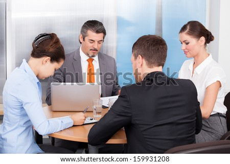 Group Of Coworkers Discussing Together In Office Meeting