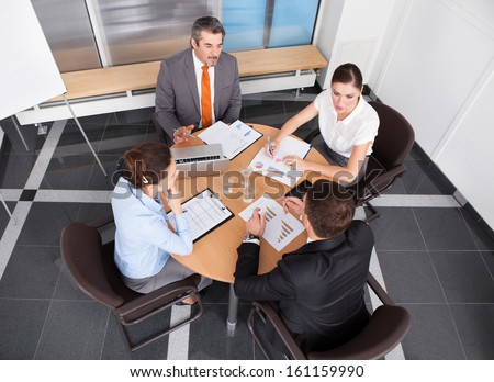Group Of Coworkers Discussing Together In Office Meeting - stock photo