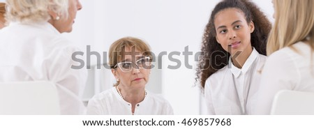 Group of creative women having business meeting, sitting in light interior, panorama