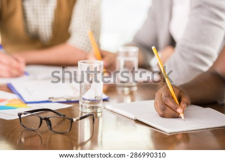 Group of creative young people dressed casual sitting at the table in office. Close-up. - stock photo