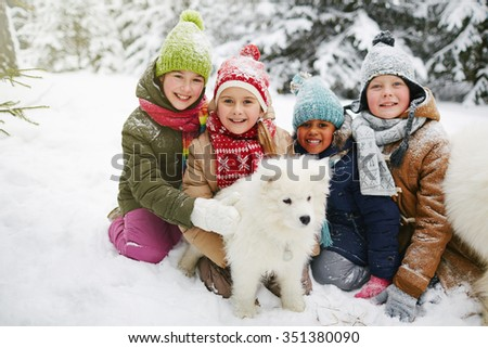 Group of cute children playing with white dog in winter park - stock photo
