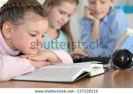 group of cute kids doing homework together at the table at home