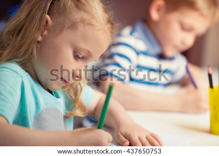 Group of cute little preschool kids drawing with colorful pencils