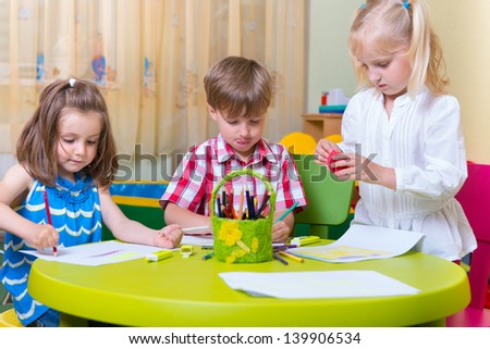 Group of cute little preschool kids drawing with crayons at the table - stock photo