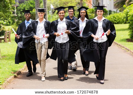 group of cute multiracial graduates walking on college campus - stock photo