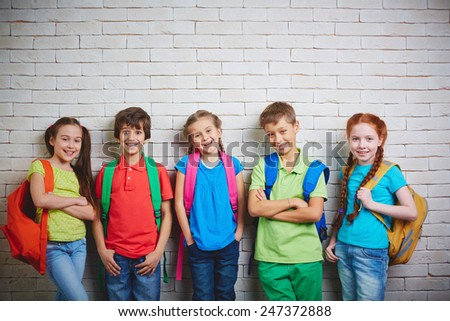 Group of cute school friends in casualwear looking at camera