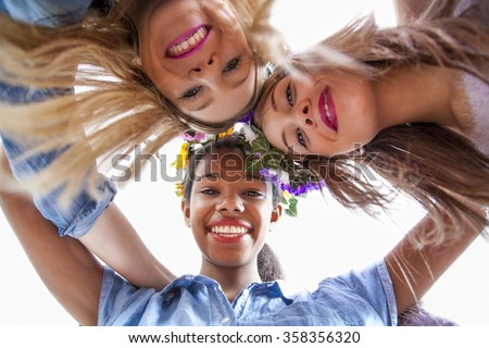 Group of cute young women of different ethnics hugging in a circle and smiling at camera  - stock photo