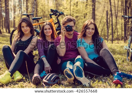 Group of cyclist taking pictures in summer forest.
