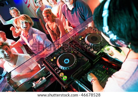 Group of dancing people in front of a dj in a discotheque - stock photo