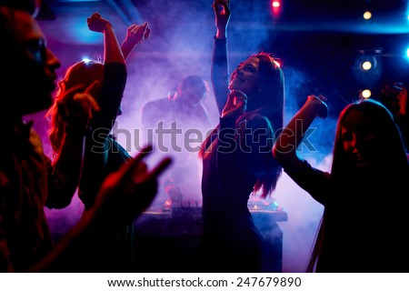 Group of dancing young people enjoying night in club - stock photo