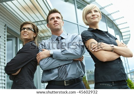 Group of dedicated young business people posing outdoor in front of office building. - stock photo