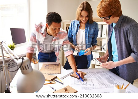 Group of designers discussing sketch at meeting - stock photo