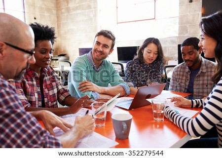 Group Of Designers Having Meeting Around Table In Office - stock photo