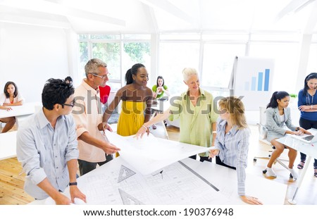Group of Designers Planning for a New Project and Discussing About the Blueprint - stock photo