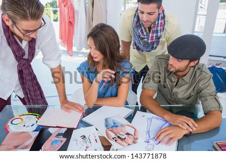 Group of designers working with photos and magazines - stock photo
