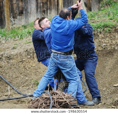 Group of determined hard co-workers pulling rope - stock photo