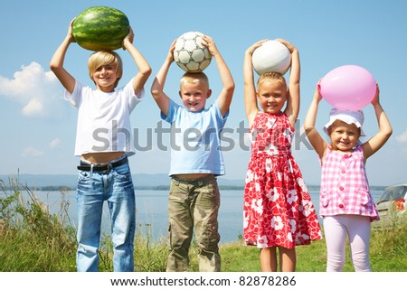 Group of different children holding a watermelon, balls and balloon - stock photo