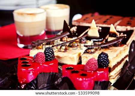 Group of different mini cakes with capuccino on background - stock photo