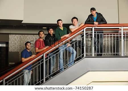 Group of Diverse College Students standing at the stairs inside a University building - stock photo