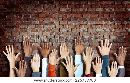 Group of Diverse Hands Raised on Brick Wall - stock photo