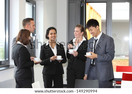 Group of diverse multiethnic businesspeople on coffee break with three ladies and two men standing together chatting in smart suits