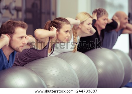 Group of diverse people in a receding line doing pilates in a gym balancing over the gym balls with their hands laocked behind their necks toning their muscles