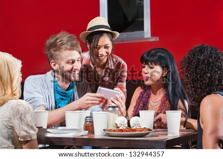 Group of diverse people laughing with phone and eating pizza