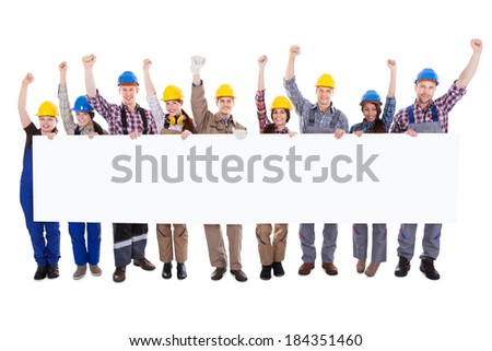 Group of diverse skilled motivated workmen and women standing in a line cheering celebrating a success holding a blank white banner with copyspace for your text on a white background - stock photo