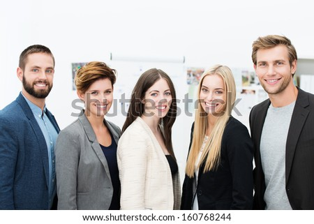 Group of diverse successful stylish young business partners or team standing in a row in the office smiling happily at the camera - stock photo