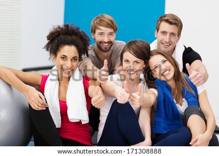 Group of diverse young athletes at the gym sitting on stairs giving a thumbs up of approval as they smile happily at the camera