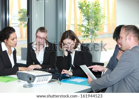 Group of diverse young multiethnic business professionals in a meeting sitting around a table discussing various documents while one woman talks on the telephone