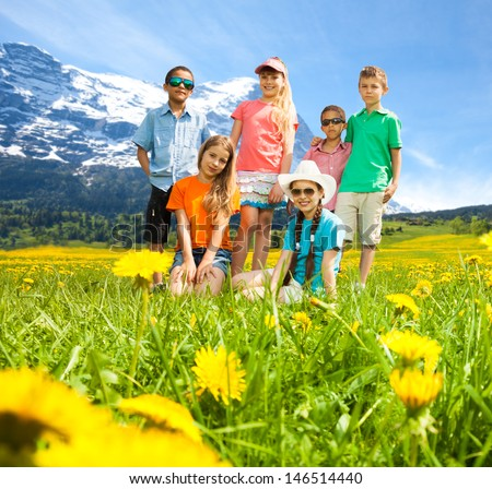 Group of diversity looking kids, boys and girls standing together in the field in mountains