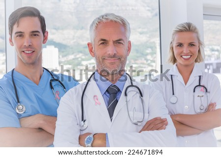 Group of doctor and nurses standing together against breast cancer awareness ribbon - stock photo