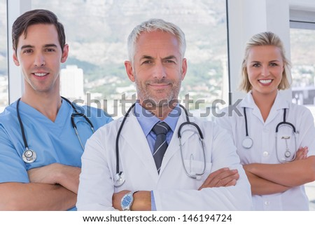 Group of doctor and nurses standing together with arms folded - stock photo