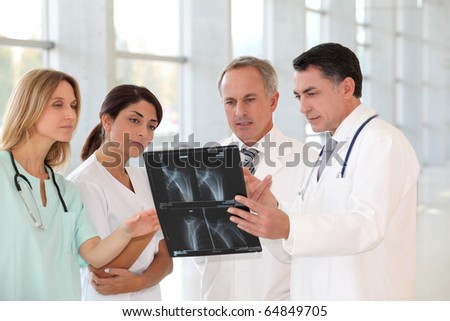 Group of doctors and nurses looking at X-ray - stock photo